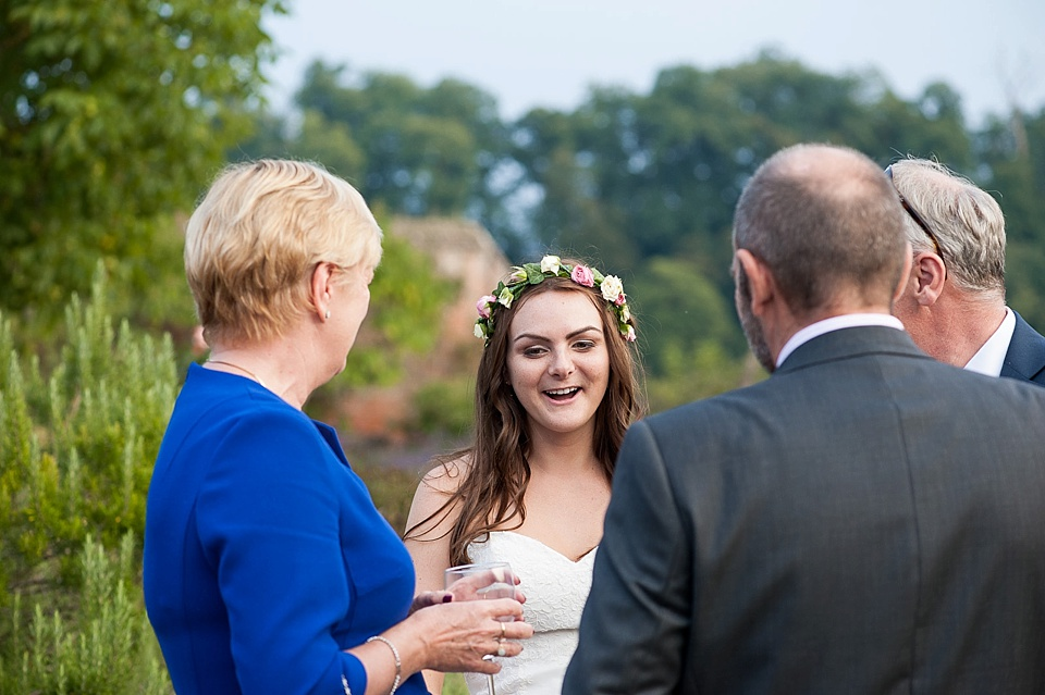 bride with real flower crown chatting to guests - English country garden wedding at the Walled Garden at Cowdray - Sussex wedding photographer © Fiona Kelly photography