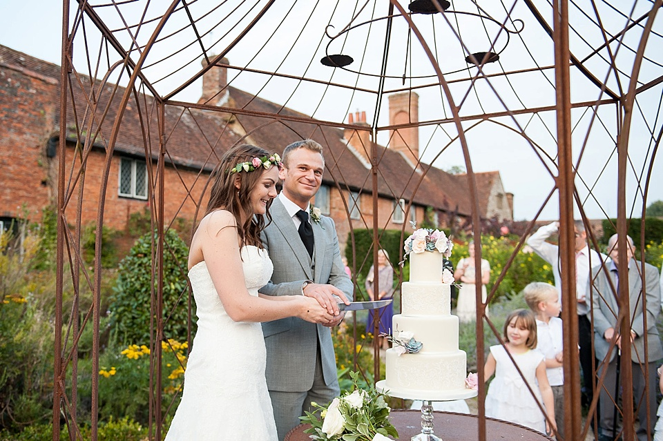 Bride and groom cutting the cake at English country garden wedding at the Walled Garden at Cowdray - Sussex wedding photographer © Fiona Kelly photography