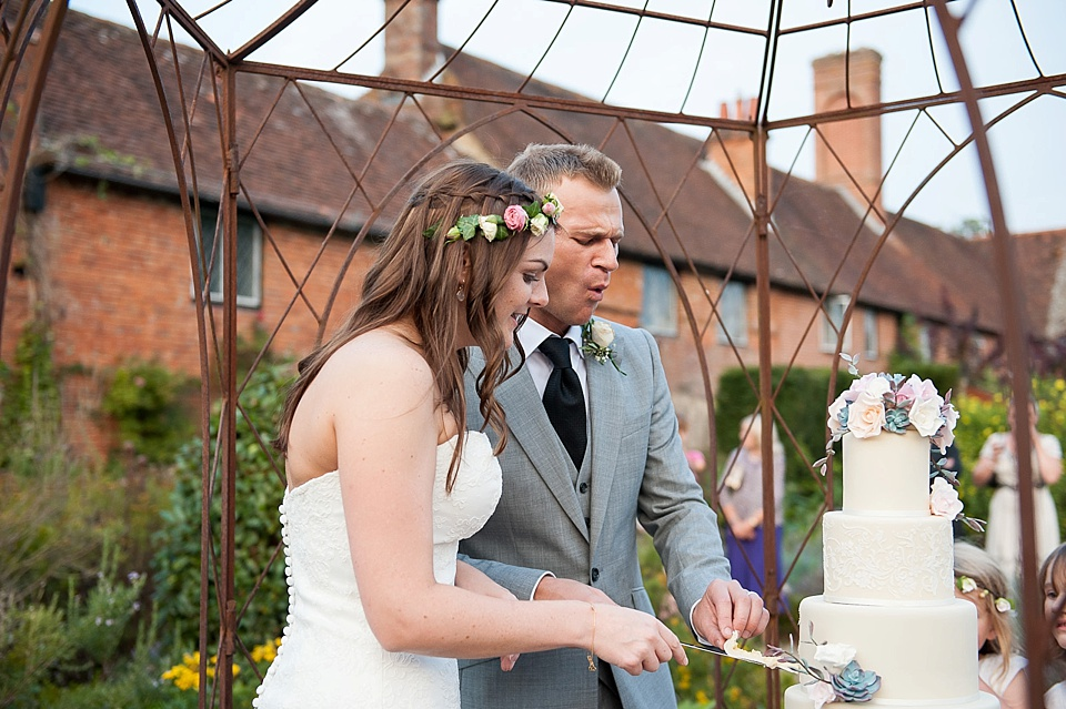 Bride in Lilian West strapless lace wedding gown cutting the cake with groom at English country garden wedding at the Walled Garden at Cowdray - Sussex wedding photographer © Fiona Kelly photography