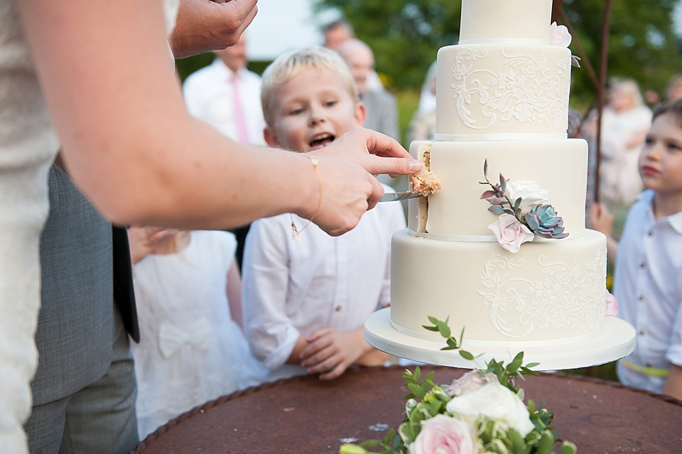 Cutting the wedding cake by Mrs Robinson's Cakes - English country garden wedding at the Walled Garden at Cowdray - Sussex wedding photographer © Fiona Kelly photography