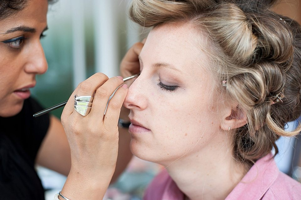 make up artist focusing on applying make up to a lady in curlers at a thames rowing club wedding, handmade wedding, scottish wedding © Fiona Kelly Photography