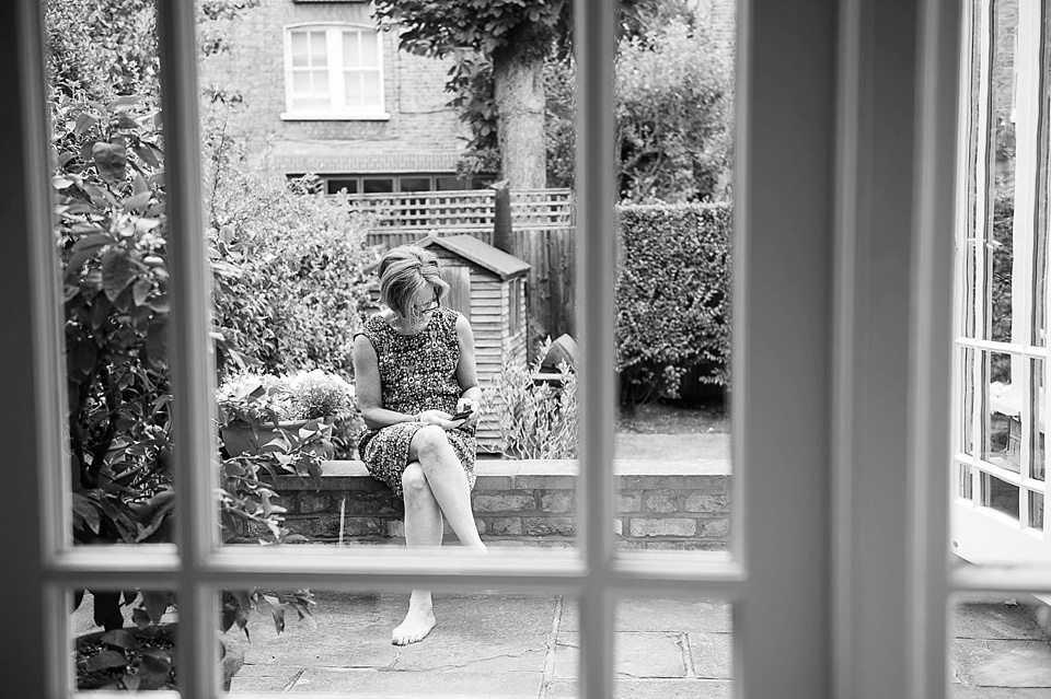 lady sitting outside texting on phone at a thames rowing club wedding, a handmade wedding, scottish wedding photographer © Fiona Kelly Photography