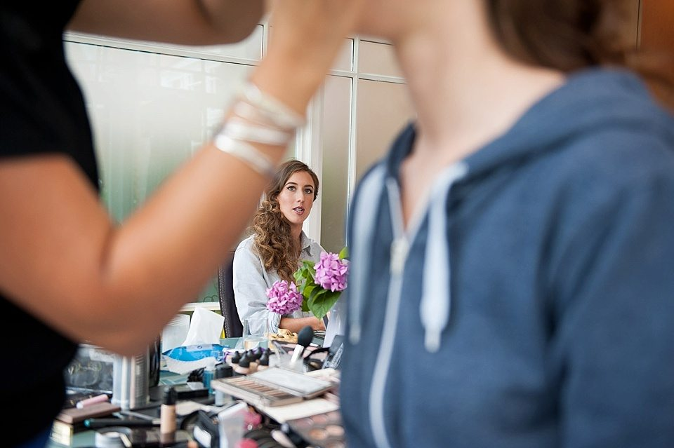 bridesmaid sitting with hair and make up finished watching bride receive her make up at a thames rowing club wedding, handmade wedding, scottish wedding photographer © Fiona Kelly Photography