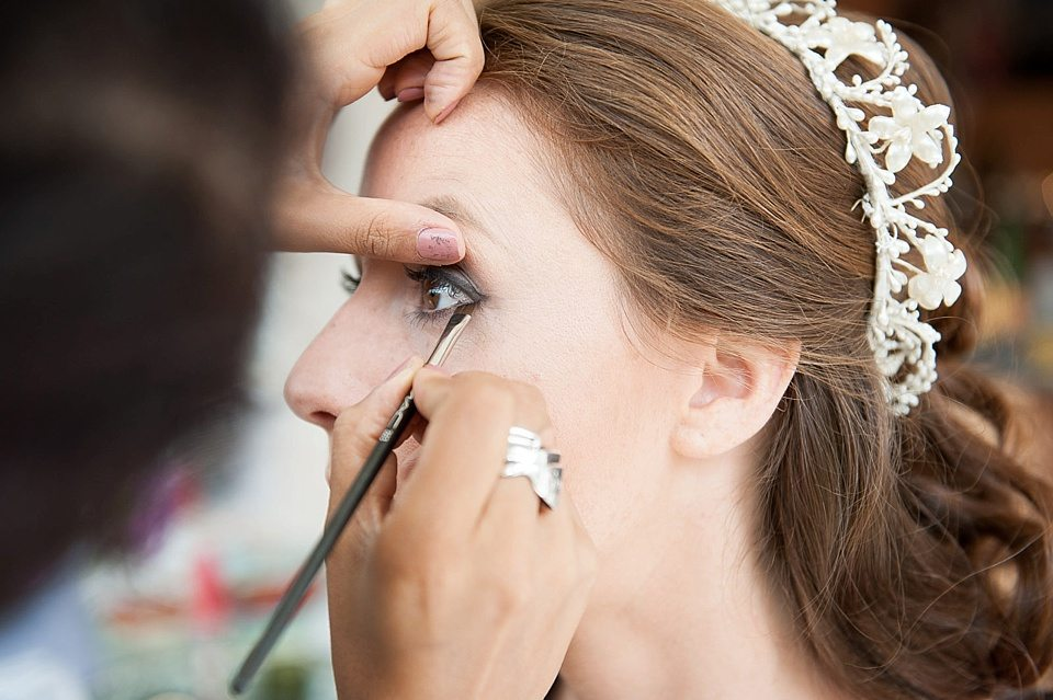 make up artists holding eyelid of bride to draw on grey eyeshadow at a thames rowing club wedding, handmade wedding, scottish wedding photographer © Fiona Kelly Photography
