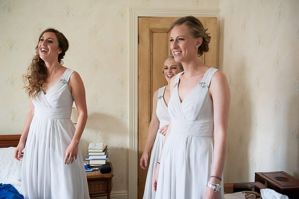 3 beautiful smiling bridesmaids wearing light grey dress with diamonte pattern on shoulder straps at a thames rowing club wedding, handmade wedding, scottish wedding photography © Fiona Kelly Photography