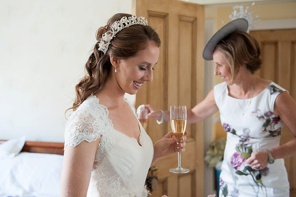 beautiful smiling bride holding a glass of champagne at a thames rowing club wedding, handmade wedding, scottish wedding photographer © Fiona Kelly Photography