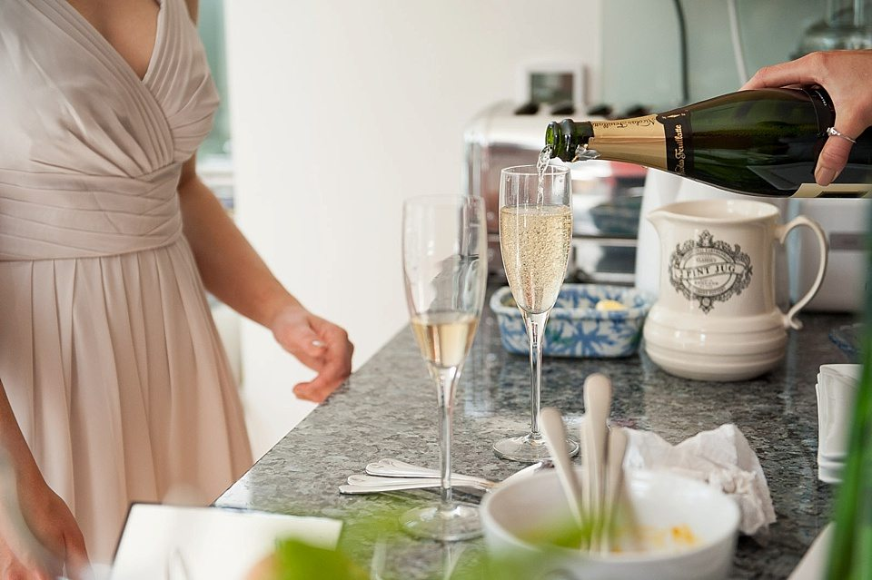 champagne being poured into a glass with bridesmaid stood by at a thames rowing club wedding, handmade wedding, scottish wedding photography © Fiona Kelly Photography