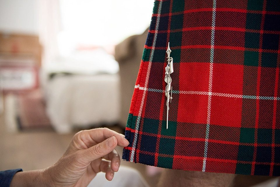 silver pin on red tartan kilt at a thames rowing club wedding, a handmade wedding, scottish wedding photographer © Fiona Kelly Photography