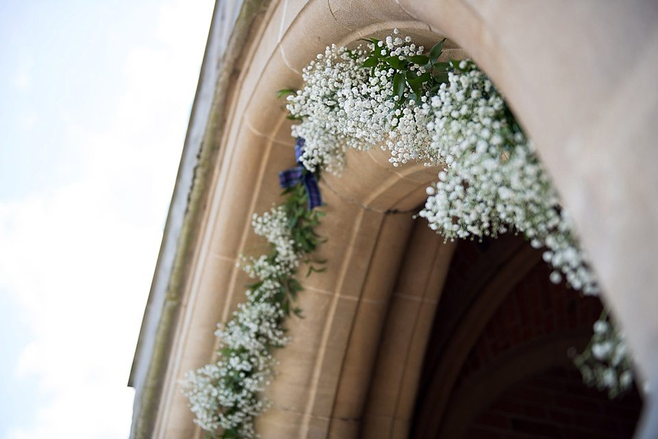flowers covering arch of door way to church at a thames rowing club wedding, a handmade wedding, scottish wedding photographer © Fiona Kelly Photography