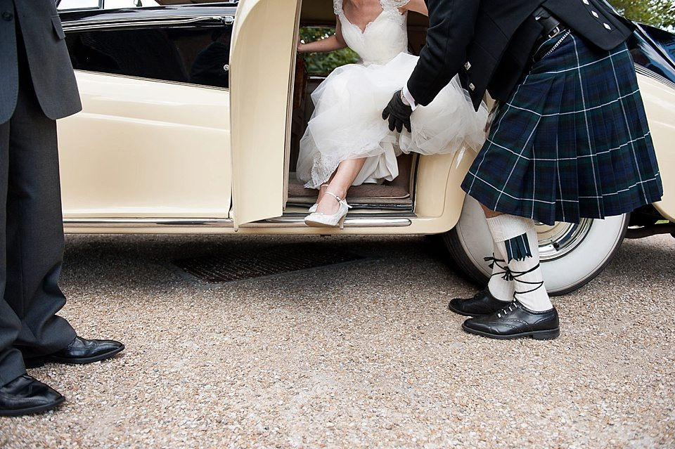 bride stepping out of vintage car outside church at a thames rowing club wedding, a handmade wedding, scottish wedding photographer © Fiona Kelly Photography