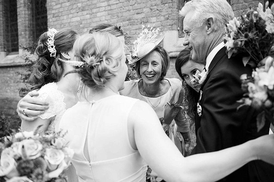 bride, mother and father of the bride and bridesmaids group hug outside church at a thames rowing club wedding, a handmade wedding, scottish wedding photographer © Fiona Kelly Photography