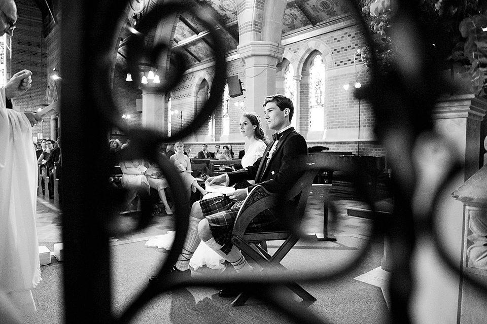 black and white shot of bridge and groom seated in church at a thames rowing club wedding, a handmade wedding, scottish wedding photographer © Fiona Kelly Photography