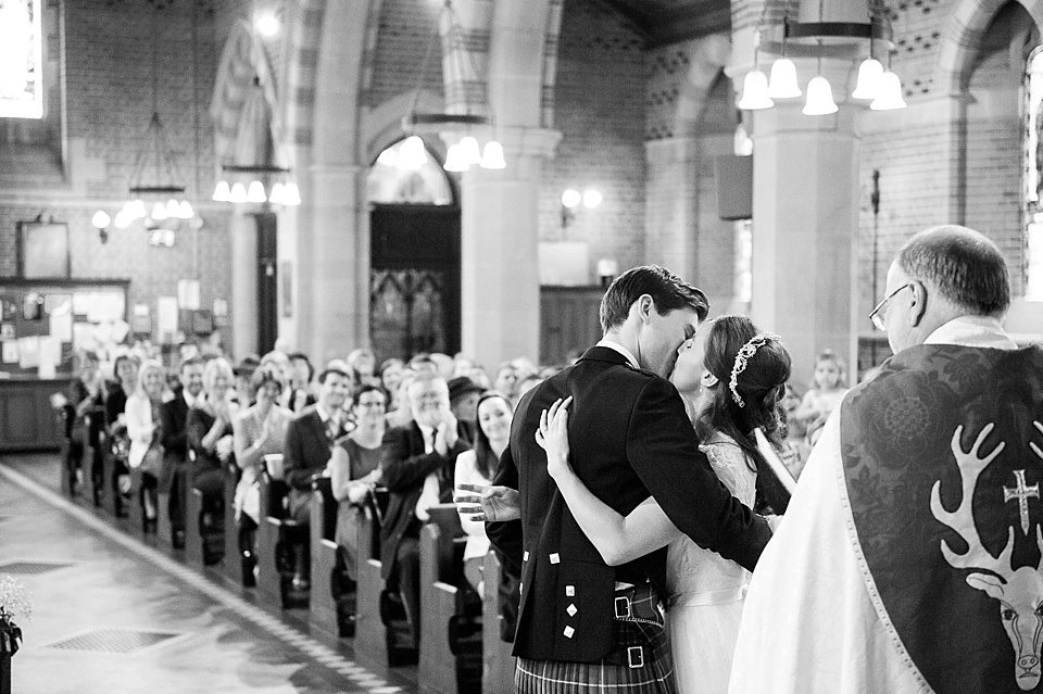 black and white image of bride and groom kissing after vows at a thames rowing club wedding, a handmade wedding, scottish wedding photographer © Fiona Kelly Photography