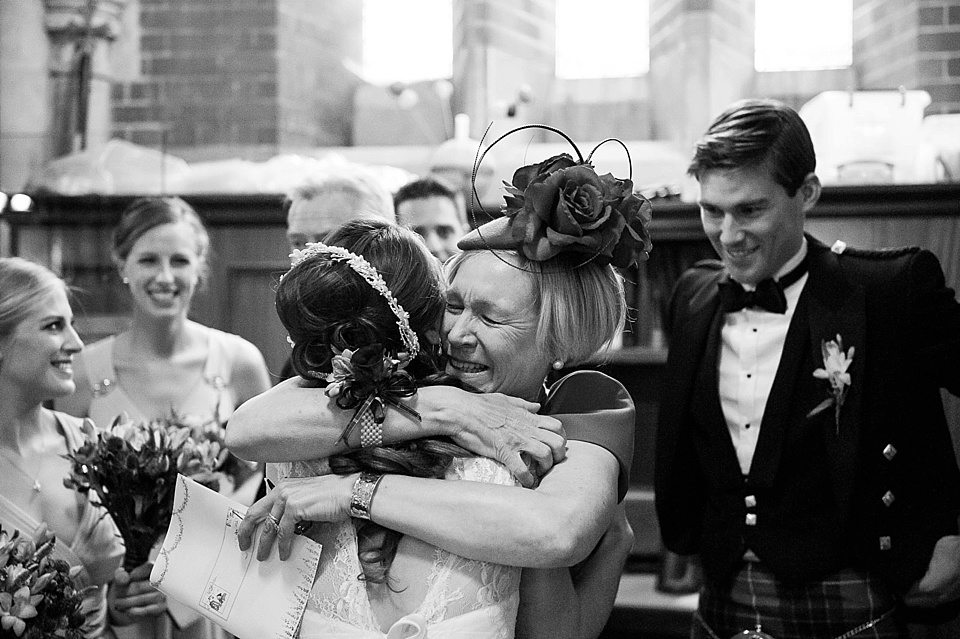 mother of the groom hugging bride in a warm embrace in church at a thames rowing club wedding, a handmade wedding, scottish wedding photographer © Fiona Kelly Photography