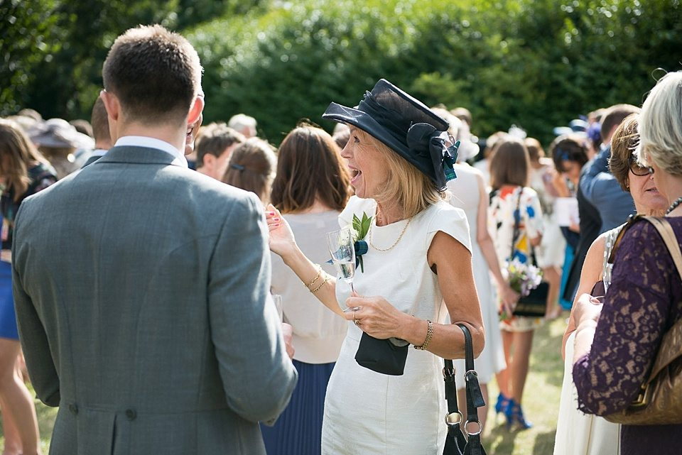 lady in black hat cheering with guests outside at a thames rowing club wedding, a handmade wedding, scottish wedding photographer © Fiona Kelly Photography