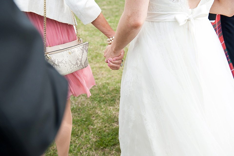 bridesmaid and bride holding hands at a thames rowing club wedding, a handmade wedding, scottish wedding photographer © Fiona Kelly Photography