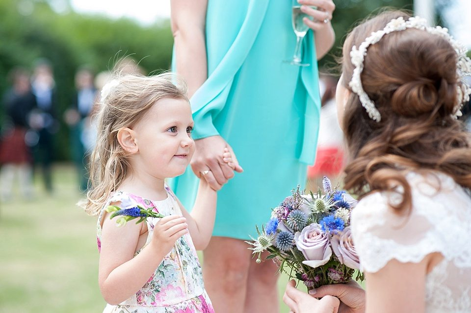 lady in aqua marine dress holding girl in flower dress with the bride at a thames rowing club wedding, a handmade wedding, scottish wedding photographer © Fiona Kelly Photography