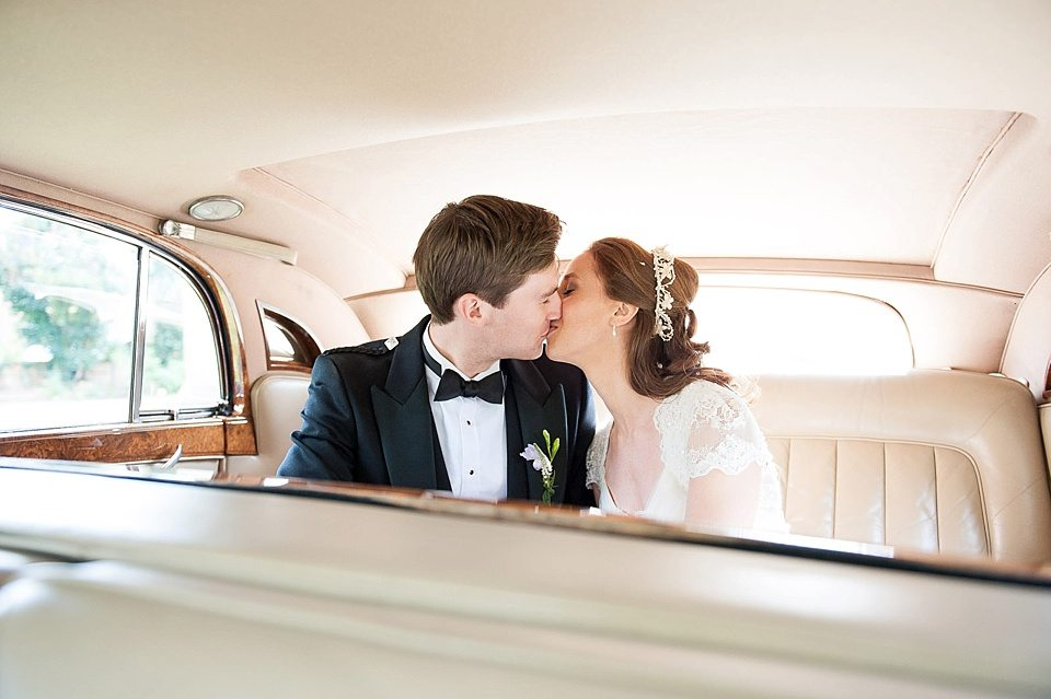 bride and groom kissing in back of vintage car at a thames rowing club wedding, a handmade wedding, scottish wedding photographer © Fiona Kelly Photography
