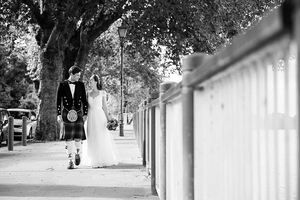 black and white shot of the bride and groom holding hands walking down the bank of the thames at a rowing club wedding, a handmade wedding, scottish wedding photographer © Fiona Kelly Photography