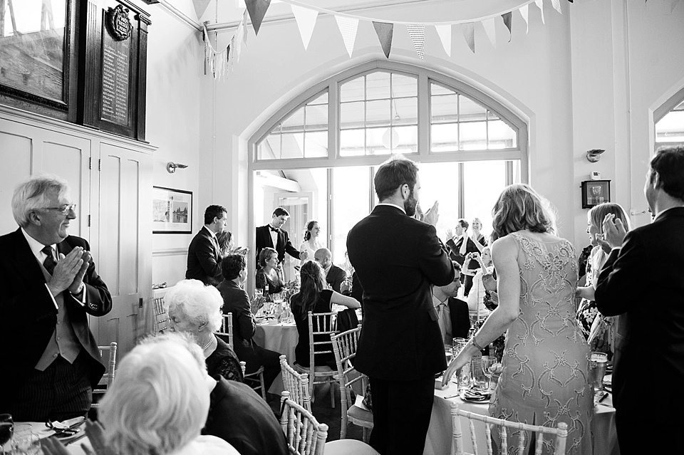 black and white shot of guests standing to applaud at a thames rowing club wedding, a handmade wedding, scottish wedding photographer © Fiona Kelly Photography