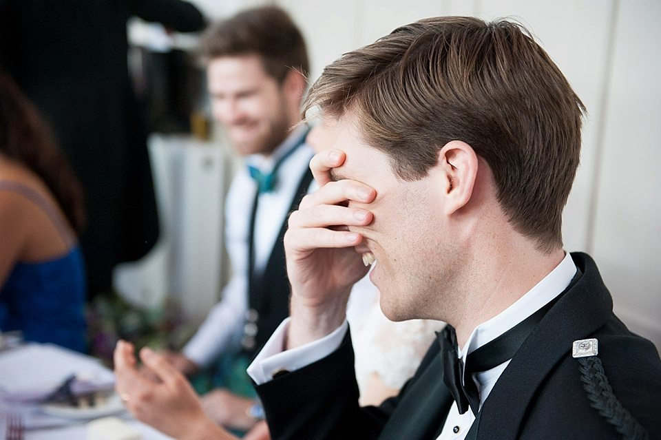 groom holding hands over eyes during speeches at a thames rowing club wedding, a handmade wedding, scottish wedding photographer © Fiona Kelly Photography