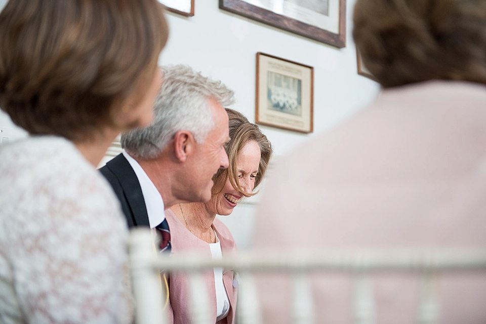 mother and father of the bride laughing during grooms speech at a thames rowing club wedding, a handmade wedding, scottish wedding photographer © Fiona Kelly Photography