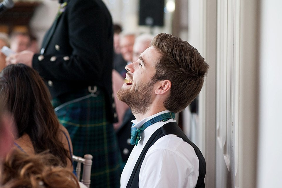 the usher laughing during speeches at a thames rowing club wedding, a handmade wedding, scottish wedding photographer © Fiona Kelly Photography