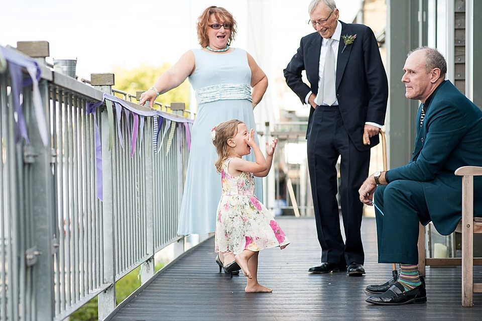 guests outside with silver gate and home-made bunting at a thames rowing club wedding, a handmade wedding, scottish wedding photographer © Fiona Kelly Photography