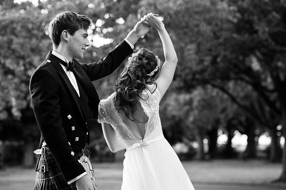black and white shot of groom twirling bride at a thames rowing club wedding, a handmade wedding, scottish wedding photographer © Fiona Kelly Photography