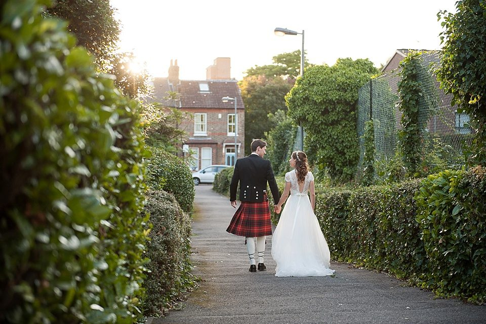 groom in kilt, bride in lace dress, walking hand in hand in putney at sunset wedding photographer © Fiona Kelly Photography