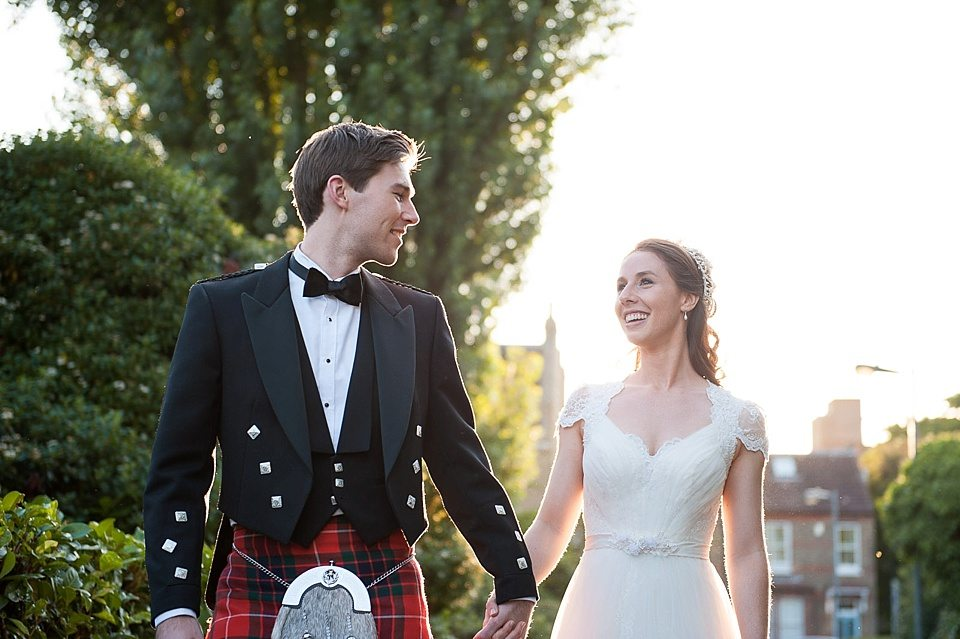 bride and groom walking hand in hand at golden hour at a thames rowing club wedding, a handmade wedding, scottish wedding photographer © Fiona Kelly Photography