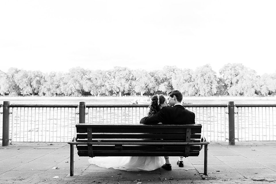 black and white shot of bride and groom sat on a bench on the river bank of the thames at a rowing club wedding, a handmade wedding, scottish wedding photographer © Fiona Kelly Photography