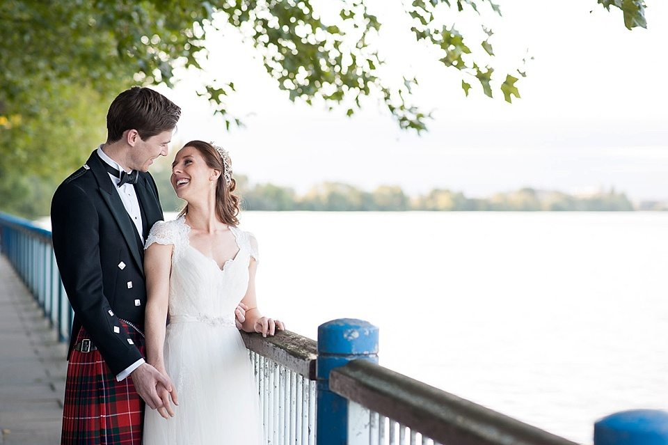 bride and groom laughing together on the river bank of the thames at a rowing club wedding, a handmade wedding, scottish wedding photographer © Fiona Kelly Photography