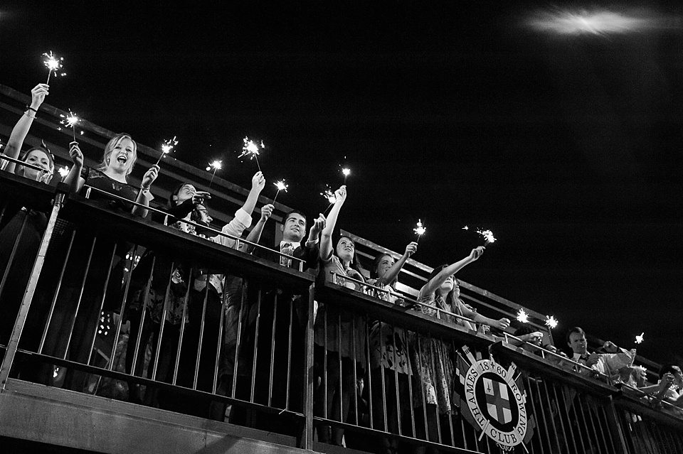 guests with sparklers over a silver fence at a thames rowing club wedding, a handmade wedding, scottish wedding photographer © Fiona Kelly Photography