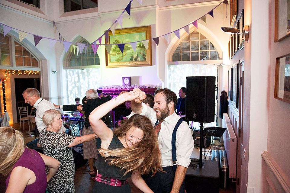 guest throwing out shapes on the dance floor at a thames rowing club wedding, a handmade wedding, scottish wedding photographer © Fiona Kelly Photography