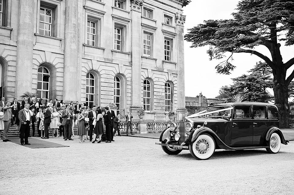 vintage-wedding-car-arrives-at-moor-park-mansion-wedding-guests-greet-elegant-summer-wedding-photography-©-Fiona-Kelly-Hertfordshire-wedding-photographer
