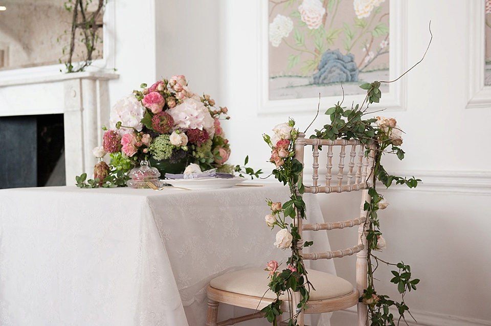 Chair covered in roses with large pink flower table arrangement - feminine bridal boudoir shoot - flowers by Indeco Flowers at The George in Rye Kent fine art photography © Fiona Kelly Photography
