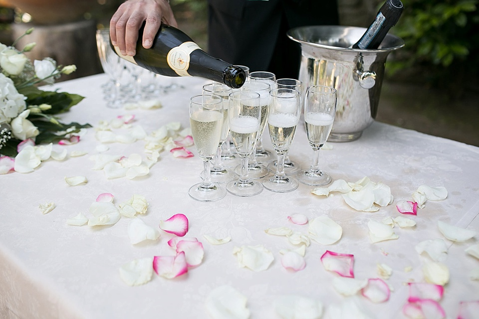 Wedding traditions - drinking champagne on a table covered in rose petals © Fiona Kelly Photography