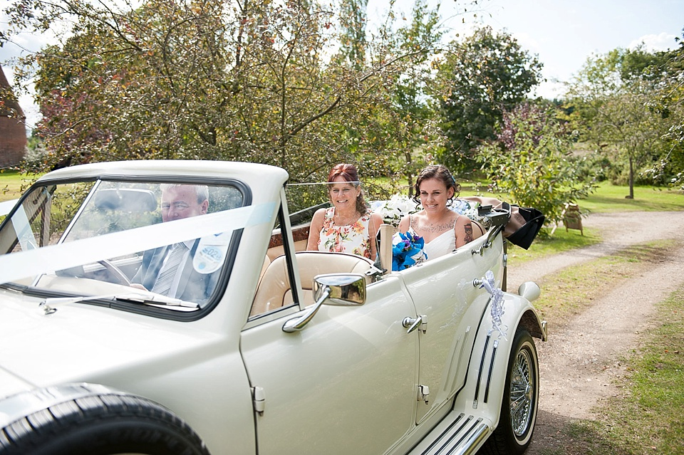 63 bride-arrives-with-mother-vintage-wedding-car-festival-garden-wedding-Ratsbury-Barn-creative-Kent-wedding-photographer-©-Fiona-Kelly-Photography