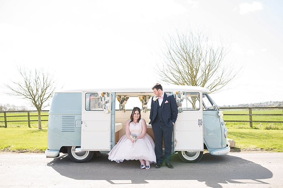 bride-in-pink-lace-dress-and-groom-with-blue-vw-camper-van-in-sunshine-photograph-fiona-kelly-photography