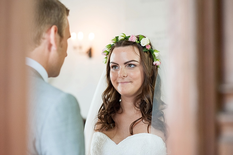 Bride wearing flower crown with groom in church wedding ceremony - natural wedding photography by Fiona Kelly