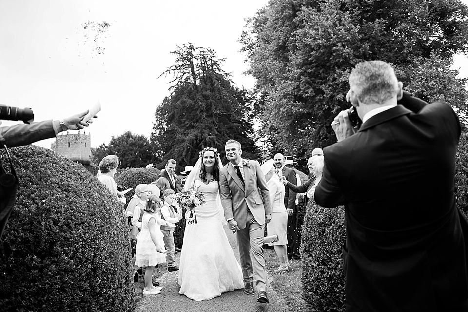 Bride and groom walking towards confetti - natural wedding photography by Fiona Kelly