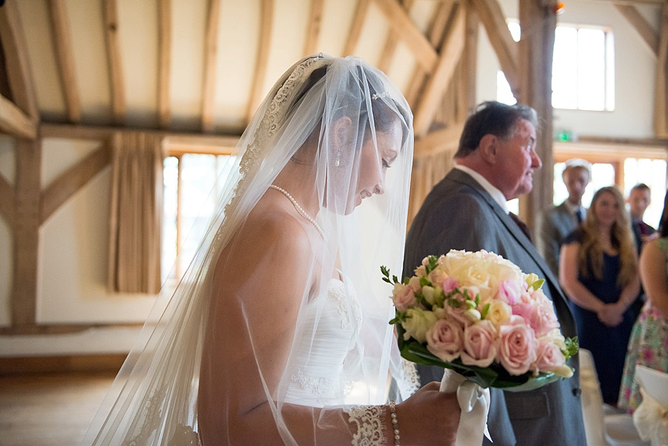 Bride with long veil and peach and pink wedding bouquet walks with father in wedding ceremony - natural wedding photography by Fiona Kelly
