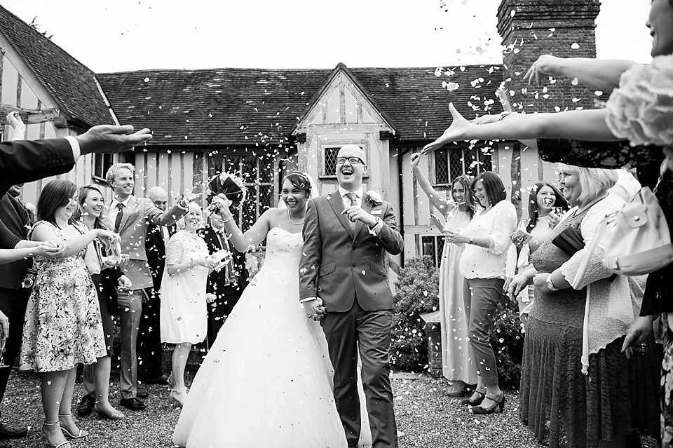 Confetti shot - bride in full wedding dress smiling with groom in black and white at historical wedding venue england - natural wedding photography by Fiona Kelly
