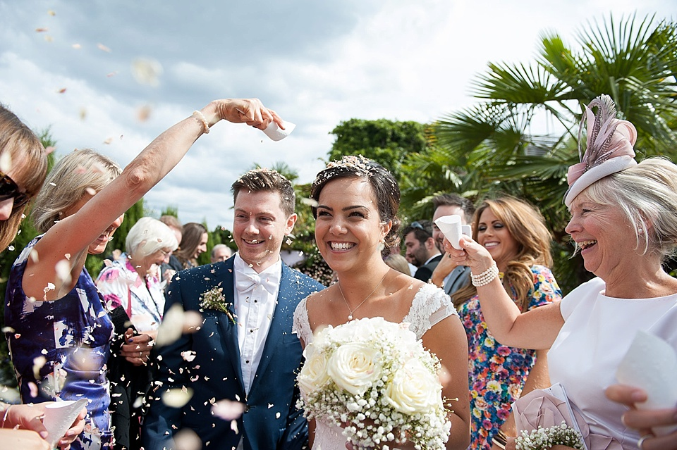 Bride and groom walking through confetti - large white rose wedding bouquet - natural wedding photography by Fiona Kelly London