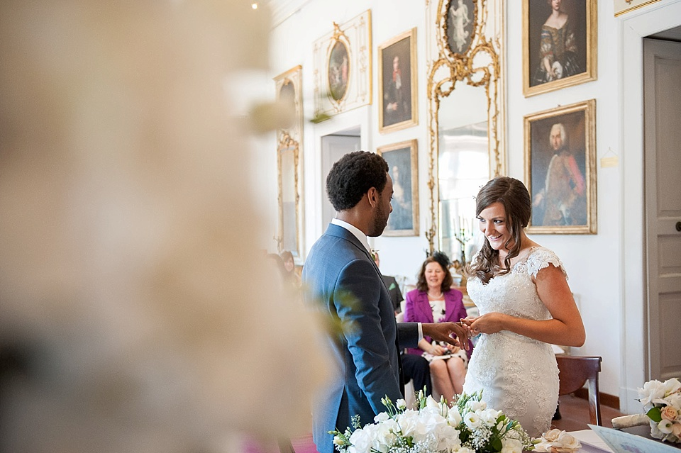 Bride with fitted lace wedding dress in church ceremony with groom in grand wedding venue - natural wedding photography by Fiona Kelly