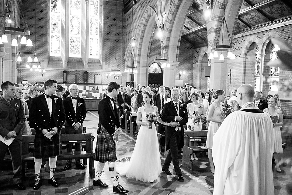 Black and white photo of bride greeting groom in kilt in church for wedding ceremony - natural wedding photography by Fiona Kelly