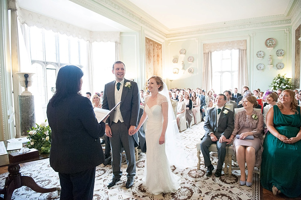 Bride with long train with groom smiling in wedding ceremony - natural wedding photography by Fiona Kelly