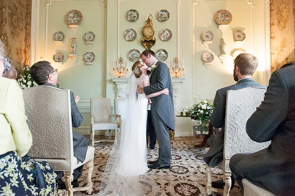 Bride kissing groom in civil wedding ceremony at grand wedding venue - natural wedding photography by Fiona Kelly