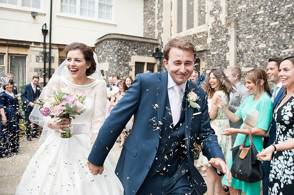 Confetti shot - Bride in stunning lace wedding dress with groom in blue suit and pink tie - natural wedding photography by Fiona Kelly